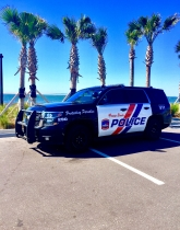 Orange Beach Police Department patrol vehicle in front of palm trees