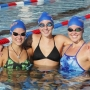 Summer league swim team - three members in posing side-by-side in pool - at Orange Beach Aquatics Center