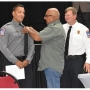 Aaron Saenz's father pins the Orange Beach Fire Rescue badge on his uniform at the graduation ceremony on Thursday, May 16 at Orange Beach Event Center