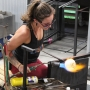 A glassblowing artist works on shaping a glass piece at the Hot Shop at Coastal Arts Center of Orange Beach