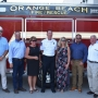 Mayor Tony Kennon and Orange Beach Fire Chief Mike Kimmerling pose with the City Council and City Administrator Ken Grimes in front of one of the new fire trucks