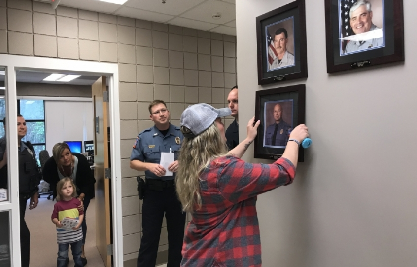 Amber Coleman hangs the photo of her late husband, Sgt. Travis Coleman