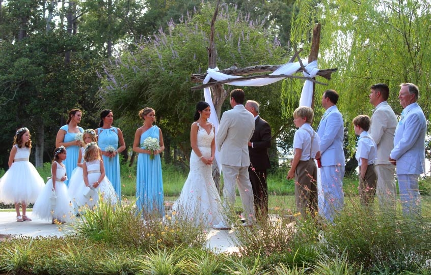 Bride and groom make their vows at the Coastal Arts Center of Orange Beach with a elegant wedding arch made out of driftwood