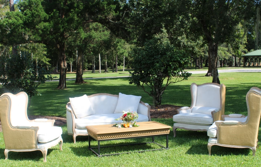 Outdoor furniture setup on the lawn of the Coastal Arts Center of Orange Beach