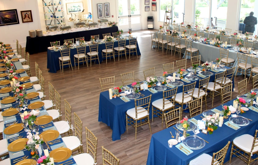 A large wedding setup with tables and all of the place settings in place in the open gallery area of the Coastal Arts Center of Orange Beach