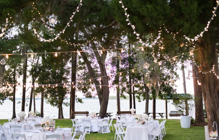 Wedding decorations at the Coastal Arts Center of Orange Beach with tables covered in white tablecloths on the lawn under trees strewn with beautiful lights and the backdrop of Wolf Bay