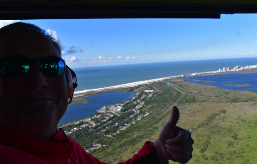 Huey helicopter flight by Friends of Army Aviation-Ozark taken on April 20, 2019 in Orange Beach with City Councilman Jeff Boyd giving the thumbs up with the picturesque Alabama shoreline in the background