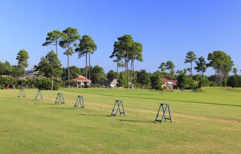 Driving range with bag stands waiting for golfers at Orange Beach Golf Center