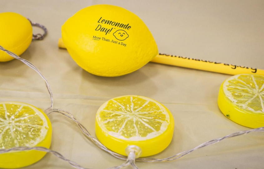 """Promotion for Lemonade Day Coastal Alabama showing a fake lemon with a """"Lemonade Day"""" logo on it and also a part of a string of decorative lemon lights."""