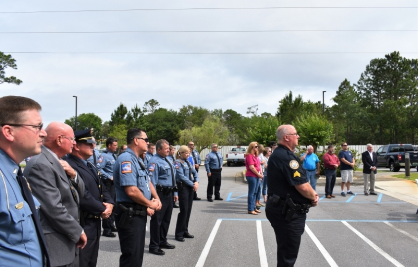 Orange Beach police officers and members of the community stand during the Orange Beach Police Department's Remember Our Fallen observance on Friday, May 10, 2019