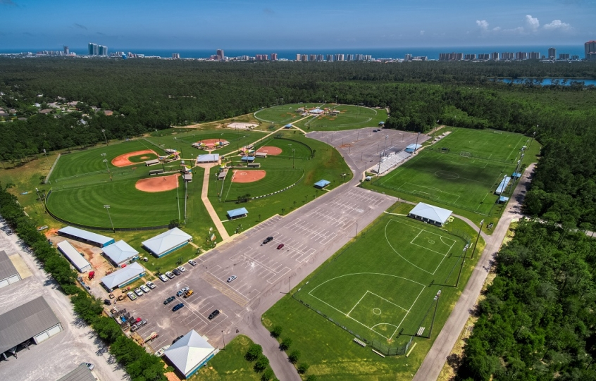 Aerial of the Orange Beach Sportsplex showing soccer fields, baseball and softball fields and parking lot with beach and condos in the distance over forested Gulf State Park.