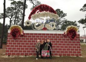 "Orange Beach city staff and Garden Club member Linda Tucker are photographed in front of decorations at City Hall in December 2017 after the city earned first place in the business category for the Orange Beach Garden Club's annual ""Light Up Orange Beach"" contest."