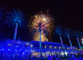 Fireworks explode over palm trees with blue light blanketing The Wharf retail stores on August 10, 2020.