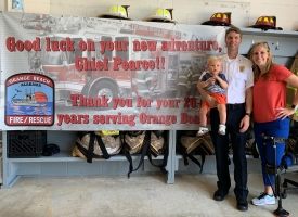 Orange Beach Fire Chief Justin Pearce poses for a photo with his wife and child in front of a banner wishing him good luck on his retirement on Tuesday, May 28, 2019.