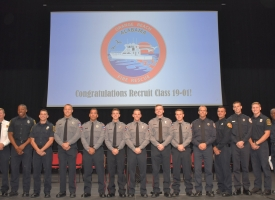 Graduating Firefighter I-II Recruit School Class 19-01 standing on stage with chiefs after graduating
