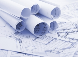 Construction plans rolled up on top of rolled out construction drawings